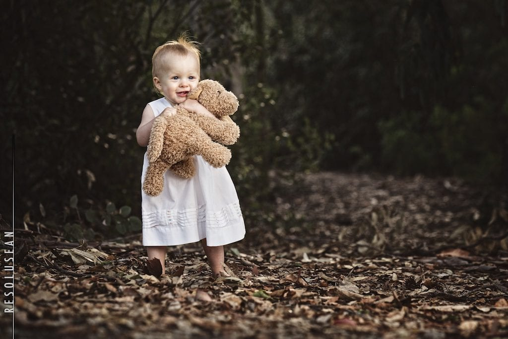 baby holding stuffed bear