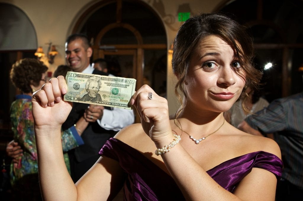 Girl holding twenty dollar bill, Tulsa wedding on a budget
