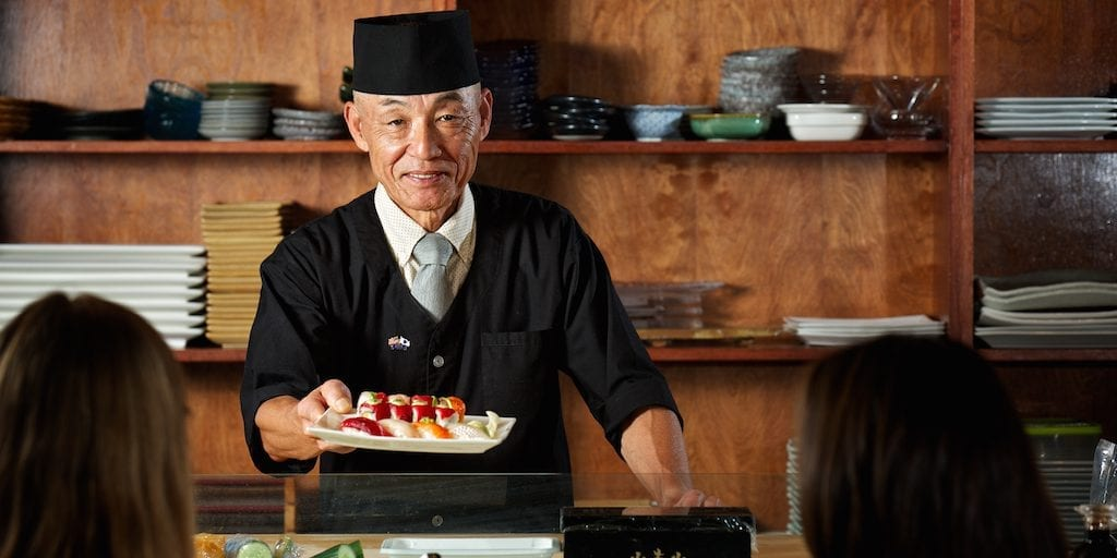 photo of sushi chef serving plate