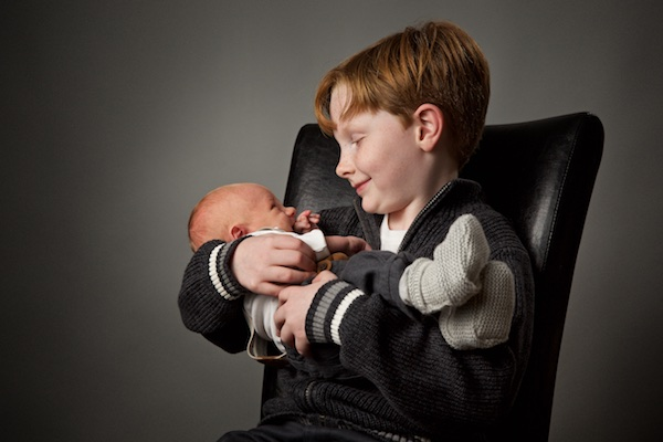 photo of boy holding baby