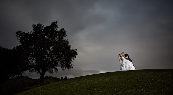 photo of bride and groom on hill